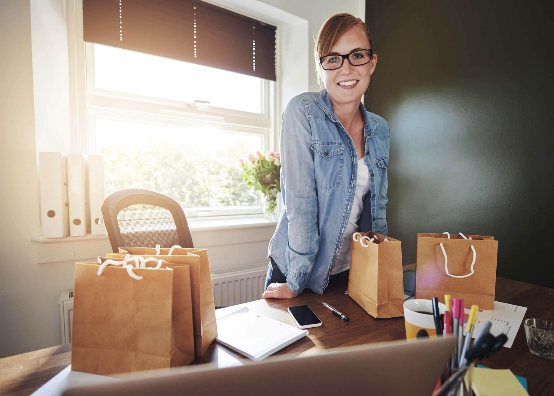 Frau mit Taschen lehtn an Schreibtisch